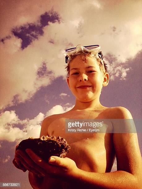 Portrait Of Smiling Shirtless Boy Holding Seashell On Beach Against Sky
