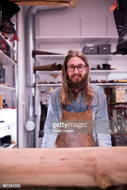 portrait of smiling shoemaker standing in workshop - schuhmacher stock-fotos und bilder