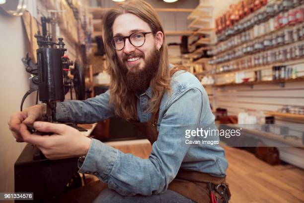 portrait of smiling shoemaker working at sewing machine in workshop - schuhmacher stock-fotos und bilder