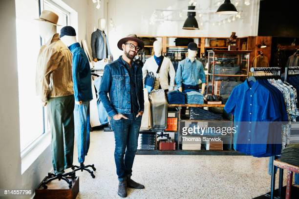 Portrait of smiling shop owner standing in mens clothing boutique