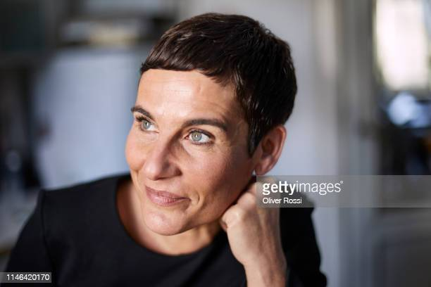 portrait of smiling short-haired woman at home looking away - 45 49 jahre stock-fotos und bilder