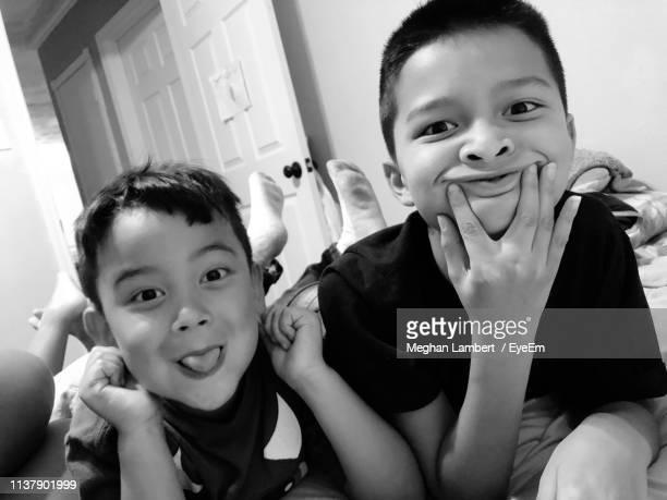 portrait of smiling siblings making faces while relaxing at home - meghan stock photos and pictures