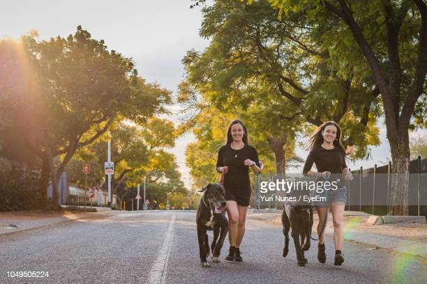 portrait of smiling sisters with dogs running on road against trees - two animals stock pictures, royalty-free photos & images