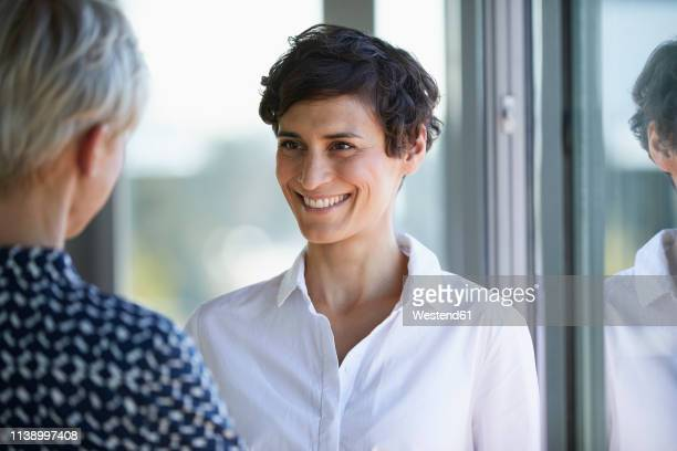 portrait of smiling smiling businesswoman looking at colleague at the window in office - german short haired pointer stock pictures, royalty-free photos & images