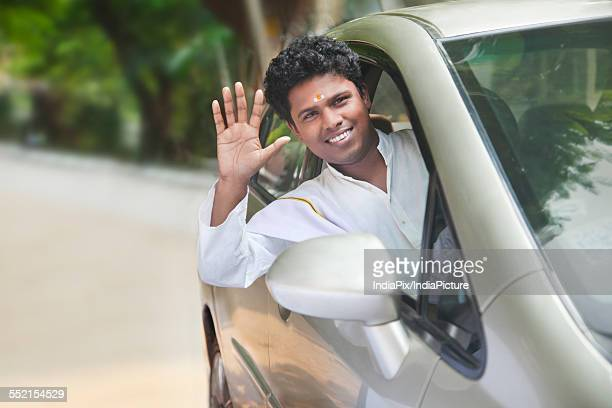 Portrait of smiling South Indian man waving out of car window
