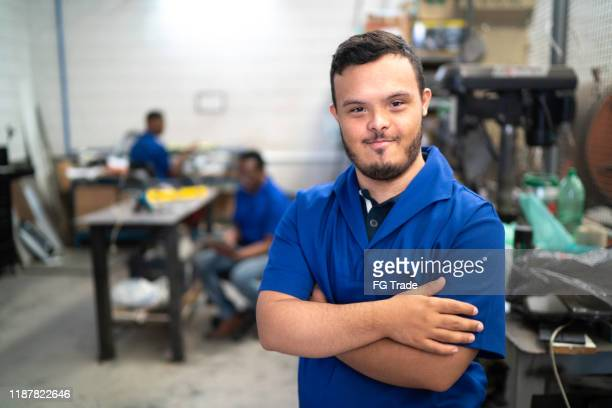 portrait of smiling special needs employee in industry - disability stock pictures, royalty-free photos & images