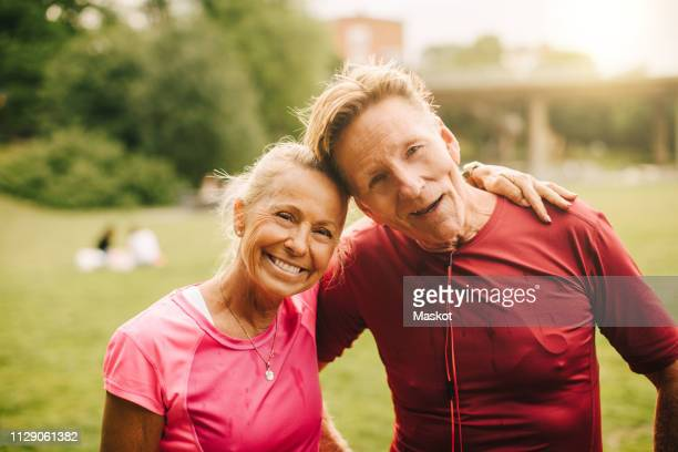 portrait of smiling sporty senior couple with head to head standing in park - disruptagingcollection stock photos and pictures