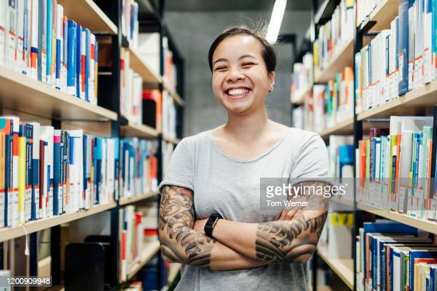 portrait of smiling student with tattoos in library - 25 29 anos imagens e fotografias de stock