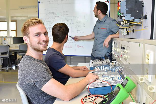 portrait of smiling student with technical instructor at whiteboard - mechatronics stock pictures, royalty-free photos & images