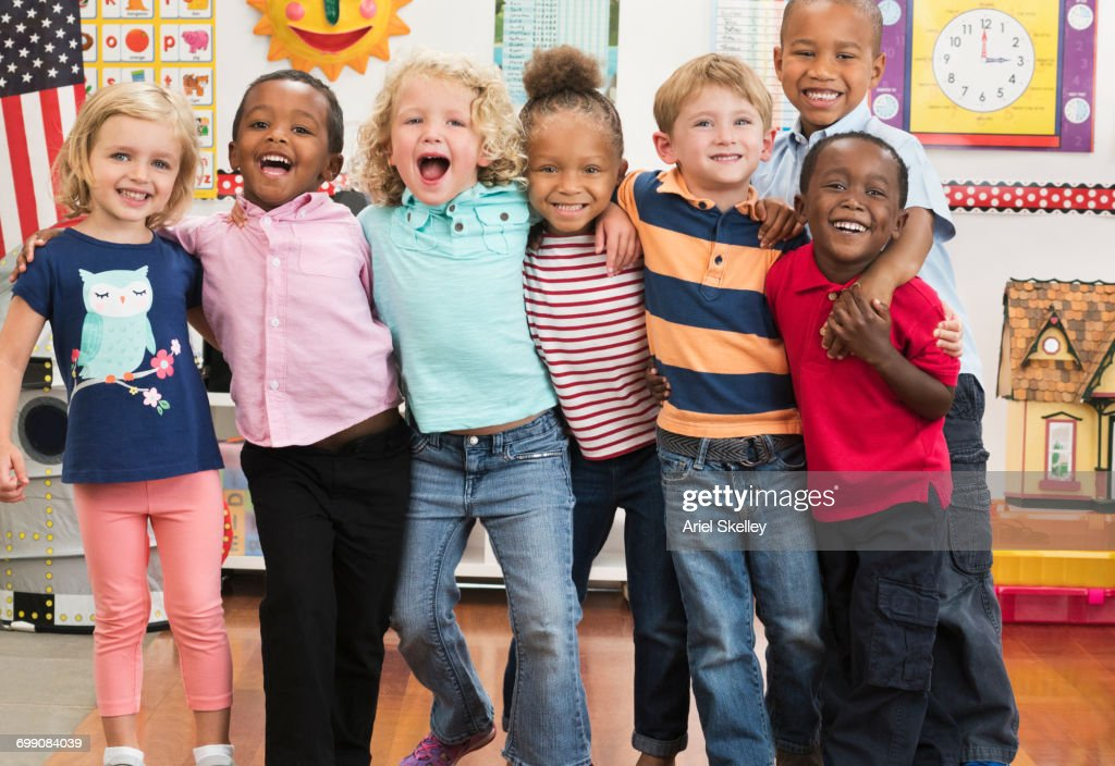 Portrait of smiling students hugging in classroom : Stock Photo