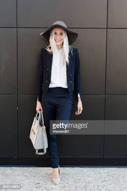 portrait of smiling stylish young woman outdoors - gray hat stock pictures, royalty-free photos & images