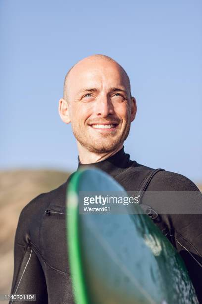 portrait of smiling surfer with surfboard - receding hairline stock pictures, royalty-free photos & images