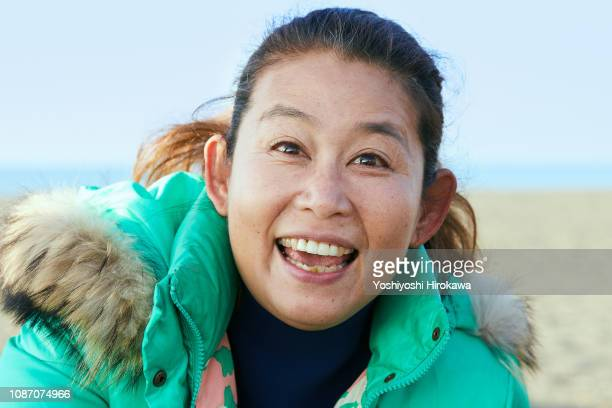 Portrait of smiling surfer woman standing on beach on the morning glow coast.