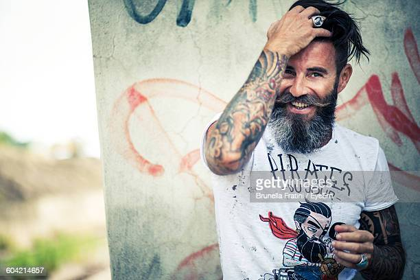 portrait of smiling tattooed hipster standing against wall - facial hair stock pictures, royalty-free photos & images