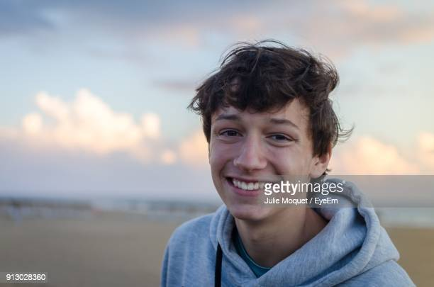 portrait of smiling teenage boy at beach against sky - tiener stockfoto's en -beelden
