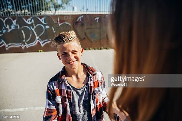 Portrait of smiling teenage boy face to face with his girlfriend