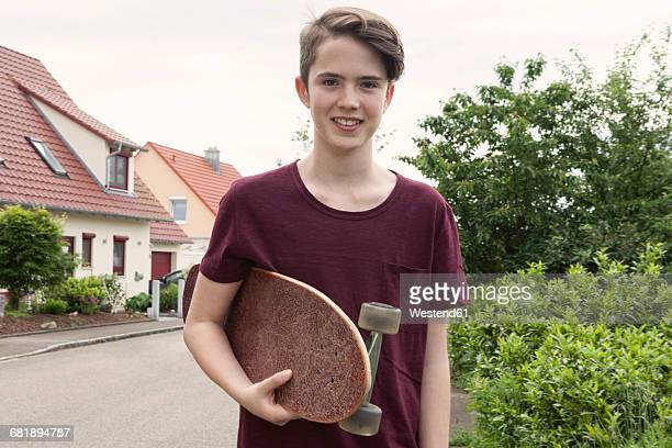 portrait of smiling teenage boy holding skateboard - 14 15 jahre stock-fotos und bilder