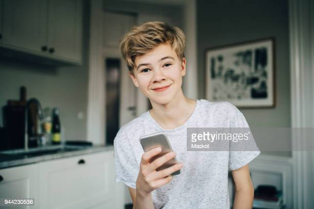 portrait of smiling teenage boy holding smart phone while sitting in kitchen at home - teenage boys stock pictures, royalty-free photos & images