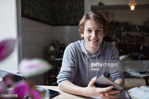 portrait of smiling teenage boy studying at home - looking at camera stock pictures, royalty-free photos & images