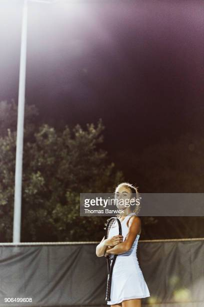 Portrait of smiling teenage female tennis player holding racquet while standing on court at night