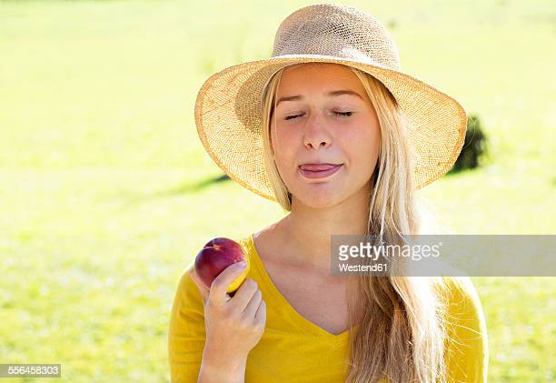 Portrait of smiling teenage girl eating a peach
