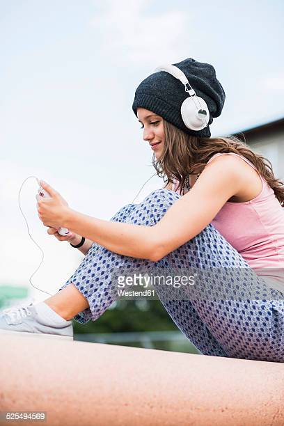 Portrait of smiling teenage girl holding smartphone hearing music with headphones