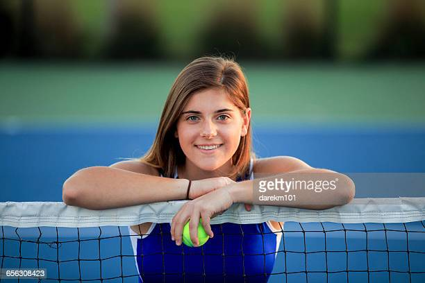 Portrait of smiling teenage girl leaning on tennis court net