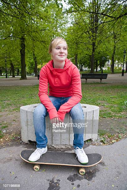 Portrait of smiling teenage girl sitting in park with skateboard
