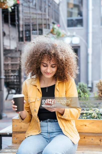 portrait of smiling teenage girl sitting on bench with coffee to go looking at cell phone - digital native stock pictures, royalty-free photos & images
