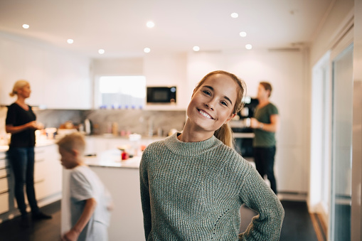 Portrait of smiling teenage girl standing against family in kitchen - gettyimageskorea