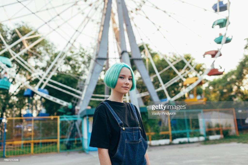 Portrait of smiling teenage girl standing against Ferris wheel at park : Stock Photo