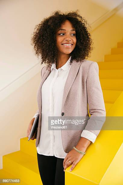 portrait of smiling teenage girl standing on yellow stairs - yellow blazer stock photos and pictures