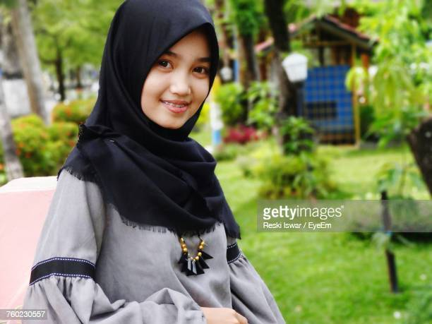 Portrait Of Smiling Teenage Girl Wearing Hijab While Standing At Back Yard