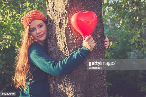 Portrait of smiling teenage girl with heart shaped balloon hugging a tree