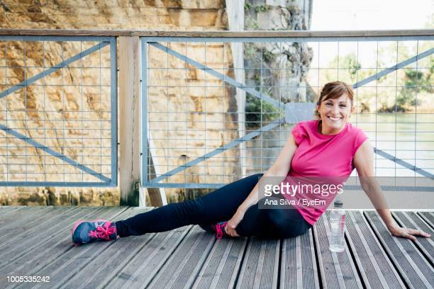 Portrait Of Smiling Tired Woman Sitting On Footbridge Over Lake