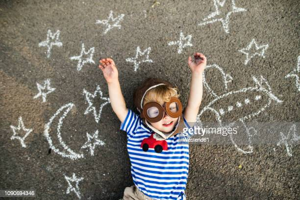 portrait of smiling toddler wearing pilot hat and goggles lying on asphalt painted with airplane, moon and stars - imagination photos et images de collection