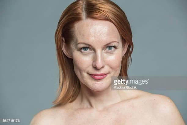 portrait of smiling topless woman against gray background - oben ohne frau stock-fotos und bilder