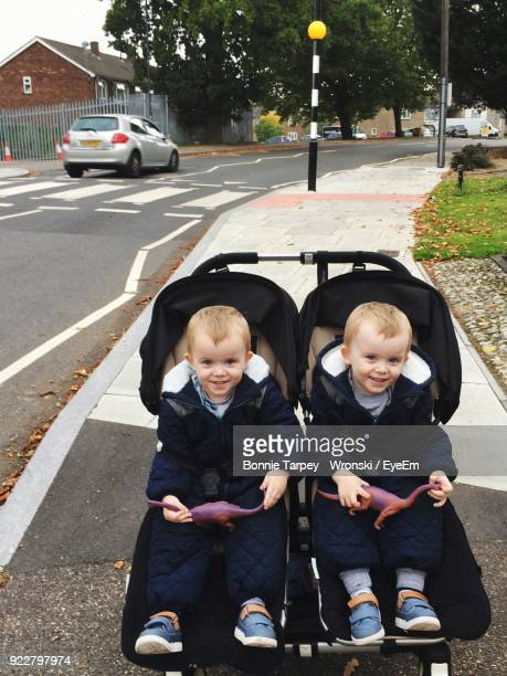 portrait of smiling twins sitting baby stroller - pushchair stock pictures, royalty-free photos & images
