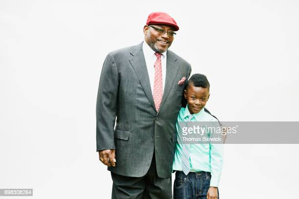 Portrait of smiling uncle and nephew embracing in front of white background