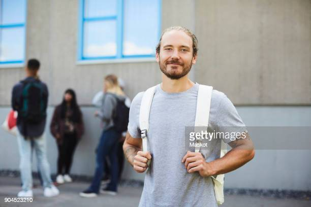 portrait of smiling university student at campus with friends standing in background - student stock-fotos und bilder