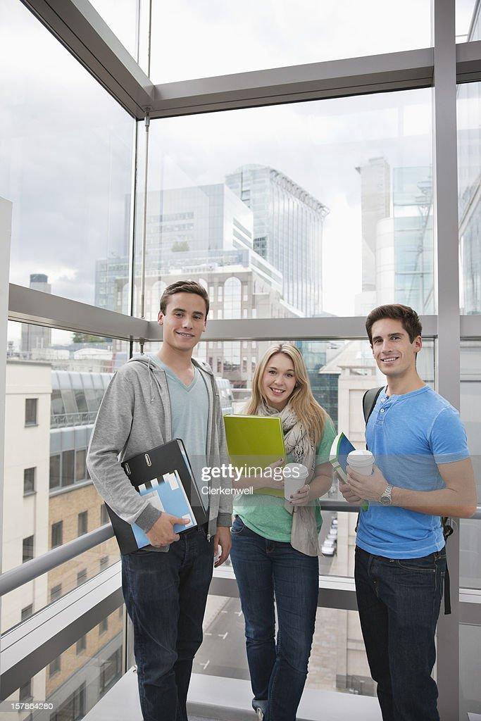 Portrait of smiling university students near window : Stock Photo