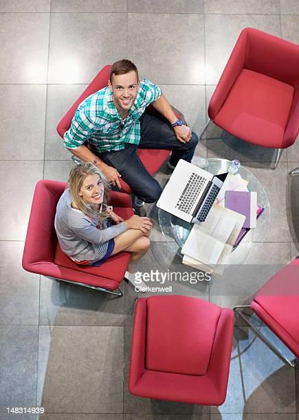 笑顔の大学の学生のポートレートラウンジで勉強