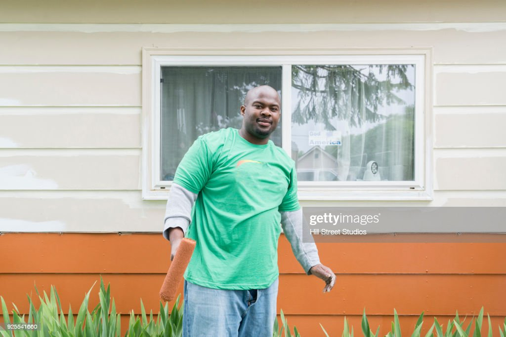 Portrait Of Smiling Volunteering Man Painting House Stock Photo