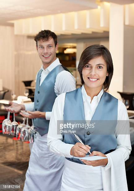 Portrait of smiling waiter and waitress in restaurant
