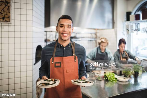 portrait of smiling waiter holding fresh food plates against female chefs in restaurant kitchen - wait staff stock pictures, royalty-free photos & images