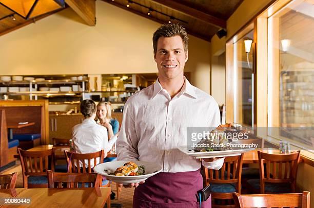 portrait of smiling waiter in restaurant - sentar se imagens e fotografias de stock