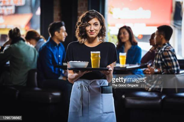 portrait of smiling waitress carrying food and drink on serving tray in bar - medium group of people stock pictures, royalty-free photos & images