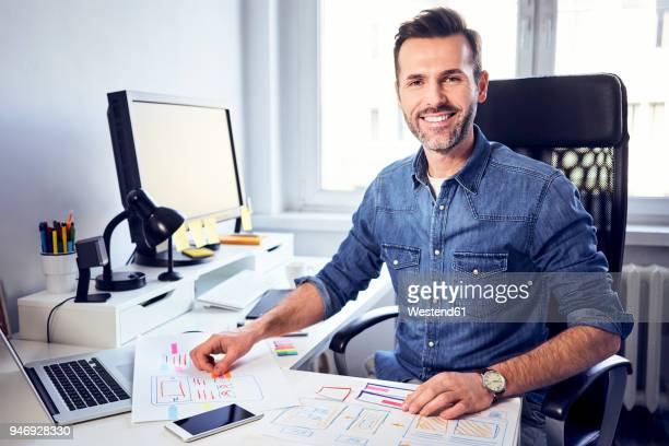 portrait of smiling web designer working on draft at desk in office - mid adult men stock-fotos und bilder