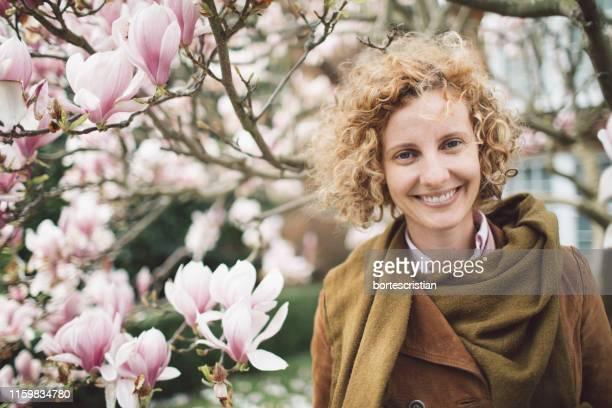 portrait of smiling woman against blooming flowers - bortes imagens e fotografias de stock