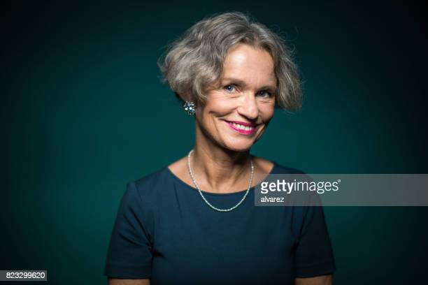Portrait Of Smiling Woman Against Green Background